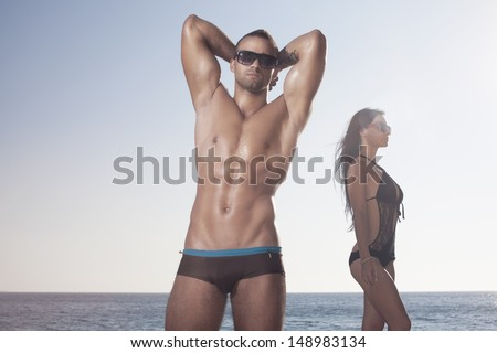 Sporty guy showing his perfect oiled body. Girl behind - stock photo