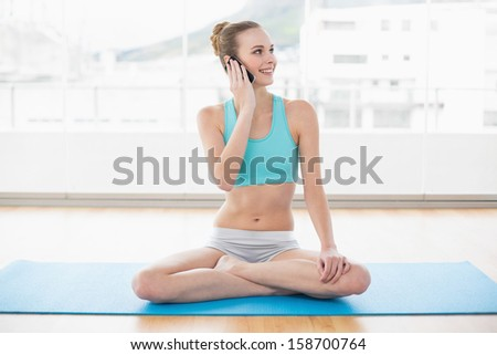 Sporty happy woman phoning and looking away in bright room