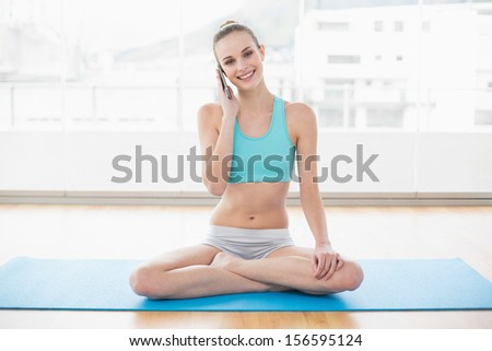 Sporty happy woman phoning in bright room