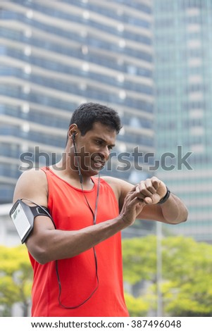 Sporty Indian man looking at his smart watch heart rate monitor. Athletic Asian man using a smart watch and listening to music with earphones. - stock photo