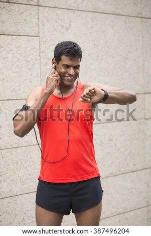 Sporty Indian man looking at his smartwatch heart rate monitor. Athletic Asian man using a smart watch and listening to music with earphones. - stock photo