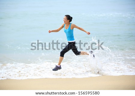 sporty lifestyle asian woman running at beach with spraying sea water  - stock photo