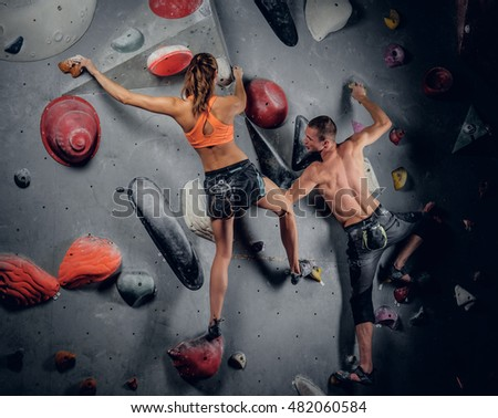 Sporty male and female climbing on an indoor climbing wall.