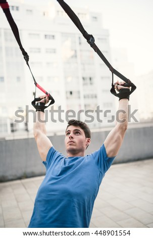 Sporty male exercising with fitness trx straps in the street - stock photo