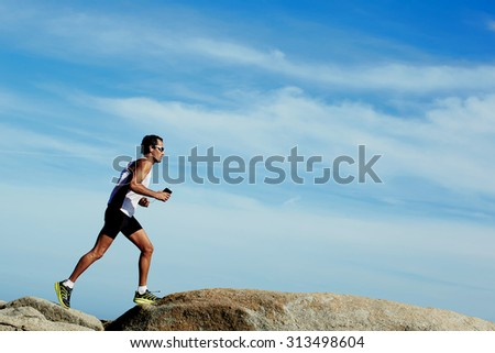 Sporty male runner jogging outdoors against copy space sky background, mature male engaged in running while listening to music in headphones, working out in mountain landscape - stock photo
