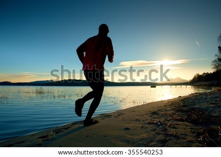 Sporty Man doing Morning Jogging on Sea Beach at Bright Sunrise Silhouettes. Running Sportsman.