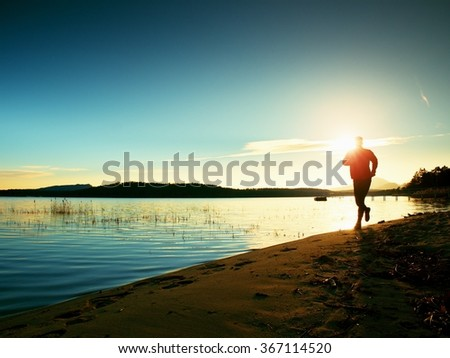 Sporty Man doing Morning Jogging on Sea Beach at Bright Sunrise Silhouettes. Running Sportsman. - stock photo