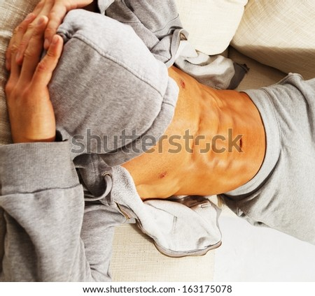 Sporty man in grey hoodie with muscular torso relaxing on sofa - stock photo