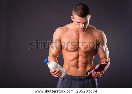 Sporty man in the gray background man holding a beer and milk and faces a choice, healthy lifestyle or alcohol. Health, sports, choice, healthy food - healthy lifestyle concept