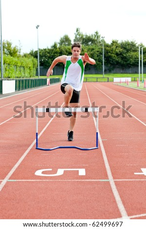 Sporty man jumping above hedge during a race in a stadium - stock photo