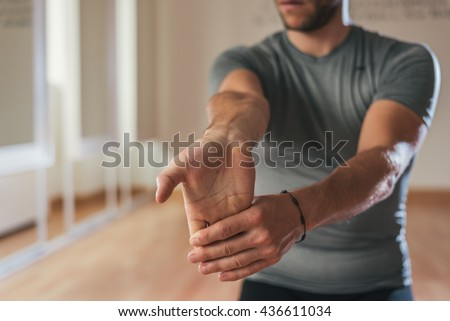 Sporty man stretching arm before gym workout. Fitness strong male athlete standing indoor warming up. - stock photo