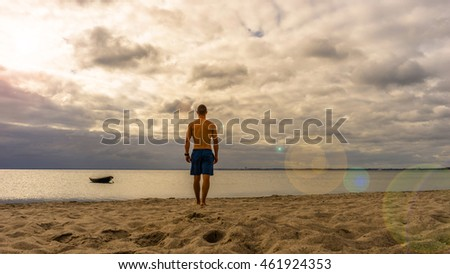 Sporty man walking to the ocean at a sunny but cloudy day, boat on the ocean