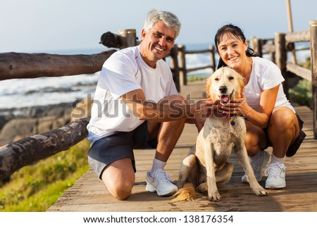 sporty middle aged couple and pet dog at the beach in the morning - stock photo