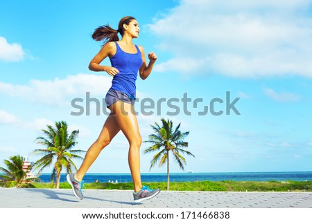 Sporty mixed race woman jogging. Color image, copy space, asian ethnicity female running with green grass and blue sky. - stock photo