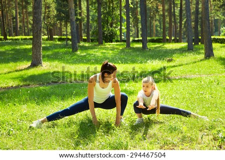 sporty mother and daughter. woman and child training in the park. outdoor sports. healthy sport lifestyle. fitness, yoga - stock photo