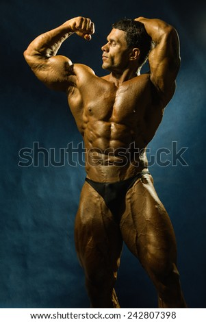 Sporty muscular man bodybuilder shows his body and strength. - stock photo