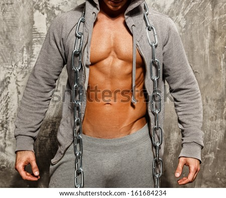 Sporty muscular man in grey hoodie with heavy metal chain - stock photo