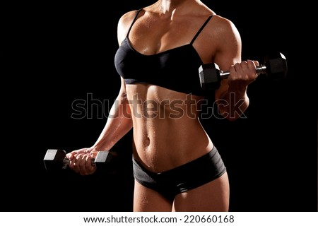 Sporty muscular woman with two dumbbells. On black background. - stock photo