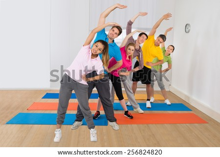 Sporty People Doing Fitness Exercise At Yoga Class - stock photo
