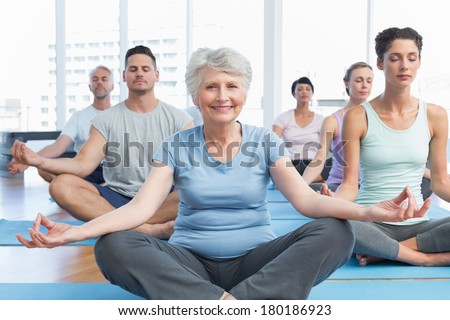 Sporty people sitting in lotus pose at a bright fitness studio