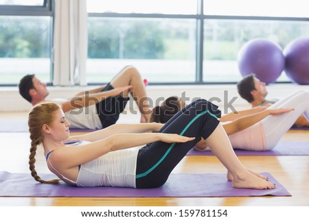 Sporty people stretching hands at yoga class in fitness studio - stock photo
