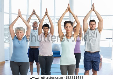 Sporty people with eyes closed and joined hands at a bright fitness studio