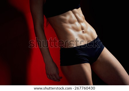 Sporty sexy girl with great abdominal muscles in black sportswear on a red wall. Fitness girl posing in the gym. Brunette in the gym. Fitness sexy girl in underwear. - stock photo