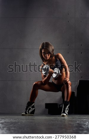 Sporty sexy girl with great abdominal muscles in black sportswear. Tanned young athletic girl with dumbbells with a nice biceps sitting on the stairs. A great sport female body. Miss fitness bikini  - stock photo