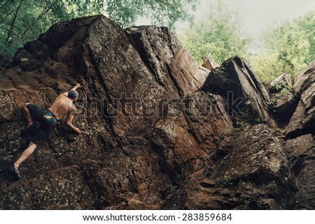 Sporty shirtless young man climbing on stone rock outdoor in summer. Space for text in right part of image - stock photo