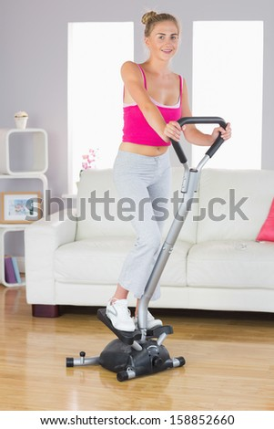 Sporty smiling blonde training on step machine in bright living room