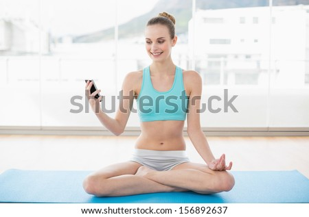 Sporty smiling woman holding smartphone in bright room