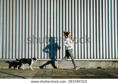 Sporty woman and dog running together for exercising.