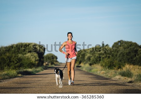 Sporty woman and dog running together on country road on summer sunset. Cheerful female athlete training and exercising outdoor with her pet. - stock photo
