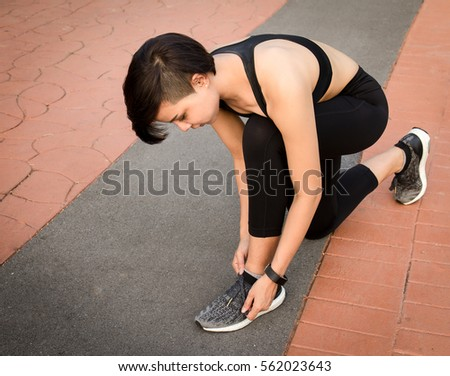 Sporty woman asian tying shoelace on running shoes before practice. Female athlete preparing for jogging outdoors.