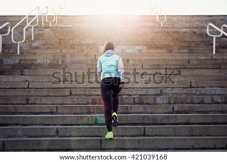 Sporty woman athlete working out running on stairs outdoors. - stock photo