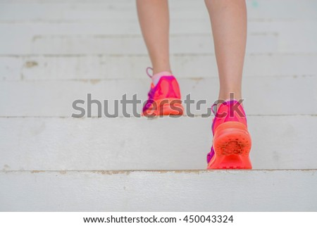 Sporty woman athlete working out running on stairs outdoors.