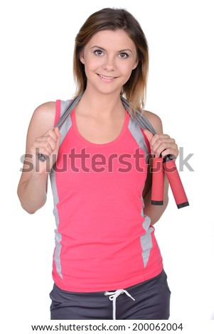 Sporty woman. Cheerful young sporty woman holding a jumping rope at her shoulders and looking at camera while standing in sport club - stock photo