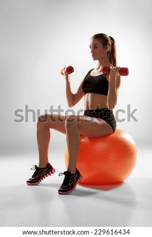 Sporty woman doing aerobic exercise with red dumbbells on a fitness ball on grey background - stock photo