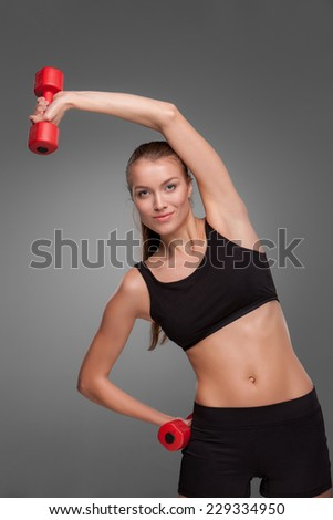 Sporty woman doing aerobic exercise with red dumbbells on grey background - stock photo