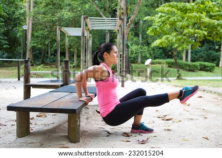 Sporty woman doing dips on left leg in outdoor exercise park - stock photo