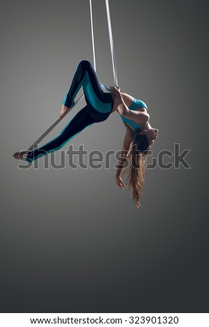 Sporty woman doing exercise with elastics, aerial straps ribbons, aerial tissues . Sport training gym and lifestyle concept. Anti-gravity yoga.  - stock photo