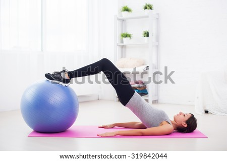 sporty woman doing pilates exercise lifting her pelvis with fit ball at home