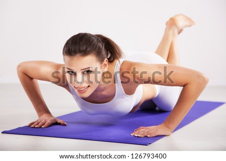 Sporty woman doing push ups in a gym - stock photo