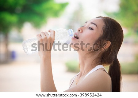 Sporty woman drinking water outdoor on sunny day - stock photo
