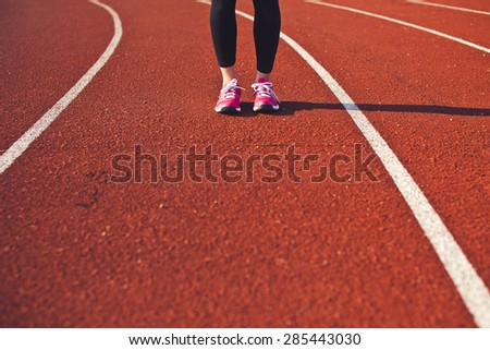 Sporty woman feet on a race track front view. Preparing for run. Brightly lit scene. Copy space