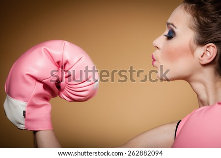 Sporty woman female boxer model wearing big fun pink gloves playing sports boxing studio shot, brown background