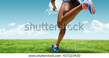 Sporty woman finishing her run against blue sky over green field
