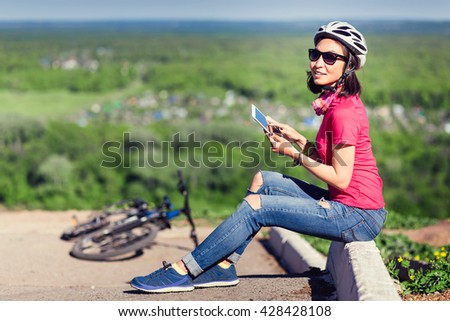 Sporty woman going to work by bicycle speaking phone in country side background