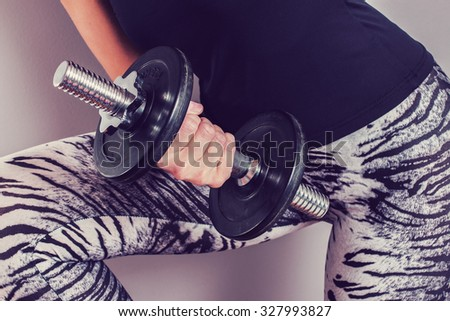 Sporty woman holding a hand weight in her hand in Finland. Focal point is dumbbells and fingers. Image includes a heavy effect.