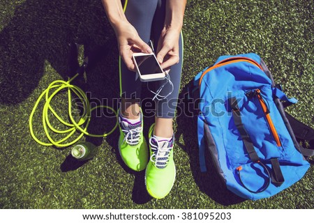 Sporty woman holding phone with empty screen sitting on the green grass with jump rope, backpack and drink bottle